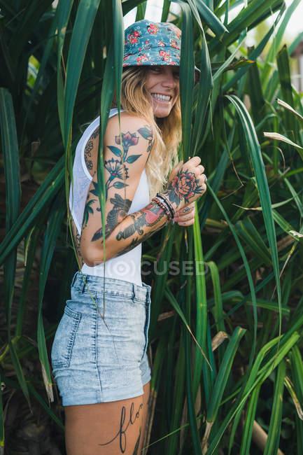 Mulher em arbustos verdes olhando para a câmera — Fotografia de Stock