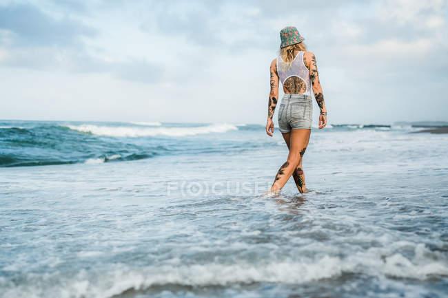 Женщина гуляет по пляжу — стоковое фото