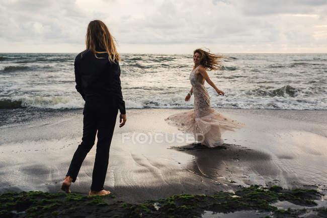 Вид сзади молодой человек, глядя на радостный женщина танцует на песчаном пляже — стоковое фото