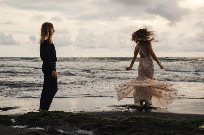 Rückansicht des jungen Mann und Frau Zeit an abgelegenen Strand bei Sonnenuntergang zu genießen — Stockfoto