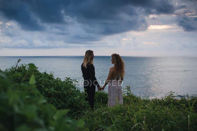 Vista trasera de la joven pareja cogida de la mano y de pie en la colina junto al mar con puesta de sol en el fondo - foto de stock