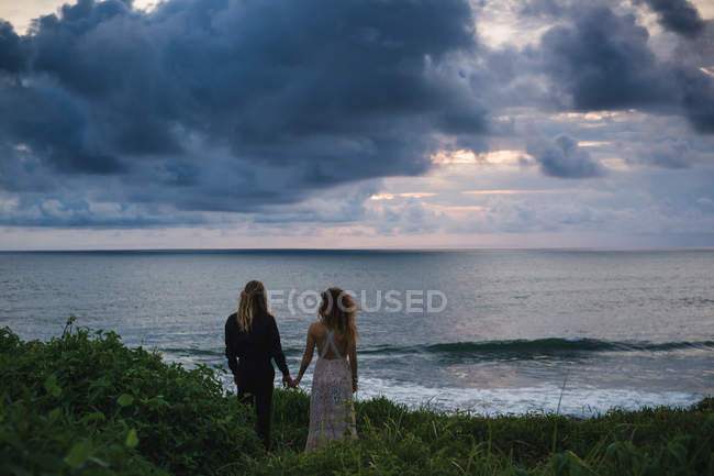 Rear view of young couple holding hands and standing on seaside hill with sunset in background — Stock Photo