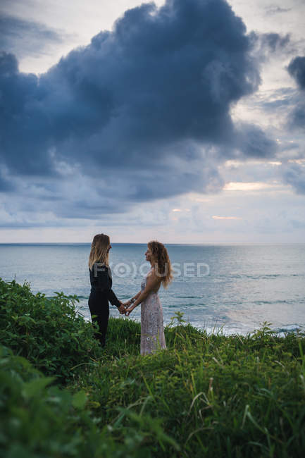 Side view of young romantic couple holding hands and looking at each other while on seaside hill — Stock Photo