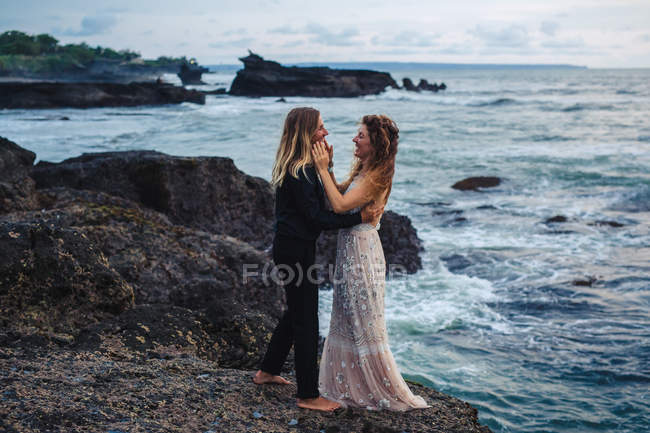 Side view of romantic couple embracing and lovingly looking at each other on seaside rocks — Stock Photo