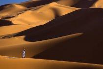 Uomo di Berber passeggiando tra dune di sabbia — Foto stock