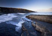 Хвилясті води над скелі на узбережжі — стокове фото