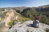 Tourist sitting on rock cliff — Stock Photo