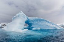 Archway formed in glacial iceberg — Stock Photo