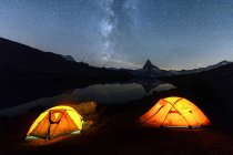 Camping under stars near lake — Stock Photo