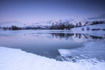 Sommets enneigés reflétées dans le lac gelé — Photo de stock