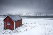 House of fishermen on snowy beach — Stock Photo