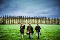 Three hunters walking on field — Stock Photo