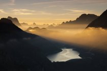 Orange light beams and mist on peaks of Dolomiti — Stock Photo