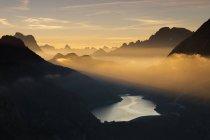Orange fasci di luce e nebbia sulle cime delle Dolomiti — Foto stock
