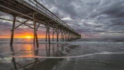 Strand mit Meeresrauschen und Pier bei Sonnenaufgang — Stockfoto