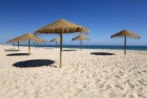 Соломенные зонтики на пустой пляж с белым песком — стоковое фото