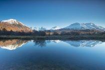 Picos nevados que se reflejan en el lago - foto de stock