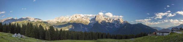 Panorama de prados y choza enmarcado por picos - foto de stock