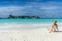 Женщина, сидя на белом песчаном пляже — стоковое фото