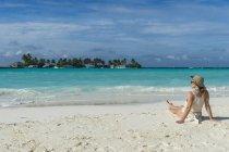 Donna seduta sulla spiaggia di sabbia bianca — Foto stock