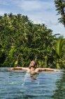 Woman enjoying overflowing pool — Stock Photo