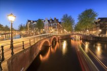 Buildings and bridges reflected in canal, Amsterdam — Stock Photo