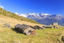 Cabanas alpinas, emolduradas pelos picos nevados — Fotografia de Stock