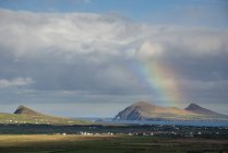 Rainbow over hills and dwellings — Stock Photo