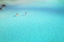People paddle boarding on emerald waters of Cala Mitjana, Menorca, Balearic Islands, Spain — Stock Photo