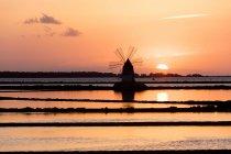 Ветряная мельница и солончаках на закате — стоковое фото