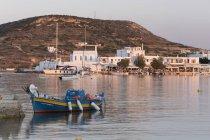 Риболовецьке судно в порту з міста на фоні на заході сонця, Pollonia, Мілош, Кіклади, Егейське море, грецькі острови, Греція — стокове фото