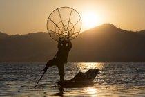 Pescatore in piedi su una gamba e tenendo pesca netto al tramonto sul Lago Inle, Shan State, Myanmar, Asia — Foto stock