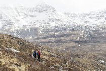 Snow covered rocky mountains and hikers, Highlands, Scotland, United Kingdom — Stock Photo