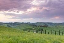 Pôr do sol sobre Agriturismo Baccoleno e caminho sinuoso com ciprestes, Asciano na Toscana, Itália, Europa — Fotografia de Stock