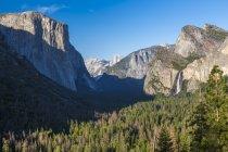Valle de Yosemite y Bridalveil Fall bajo el cielo azul, Parque Nacional de Yosemite, California, Estados Unidos, América del norte - foto de stock