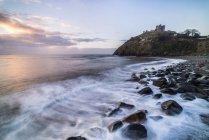 Château de Criccieth sur la falaise surplombant la plage de Criccieth au lever du soleil, Gwynedd, pays de Galles, Royaume-Uni — Photo de stock