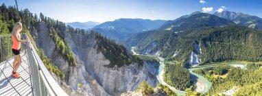 Панорамний вид на Рейн ущелині (Ruinaulta) з тераси Il Spir і жіночий турист дивиться на вид, Флімс, район Imboden, Кантон Grisons (Graubunden), Швейцарія, Європа — стокове фото