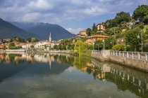 Vista de Mergozzo reflejando en lago Mergozo, Piamonte, Italia, Europa - foto de stock