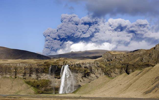 Cascata di Seljalandsfoss con pennacchio di cenere dell'eruzione Eyjafjallajokull — Foto stock