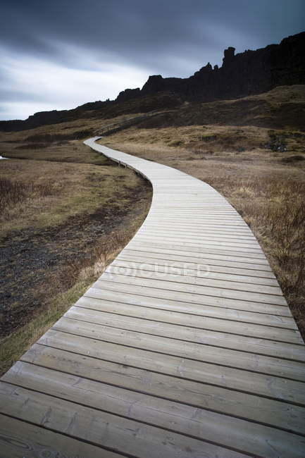 Boardwalk meandering towards rugged cliffs — Stock Photo