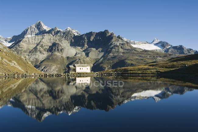 Reflection of house and mountains in lake — Stock Photo