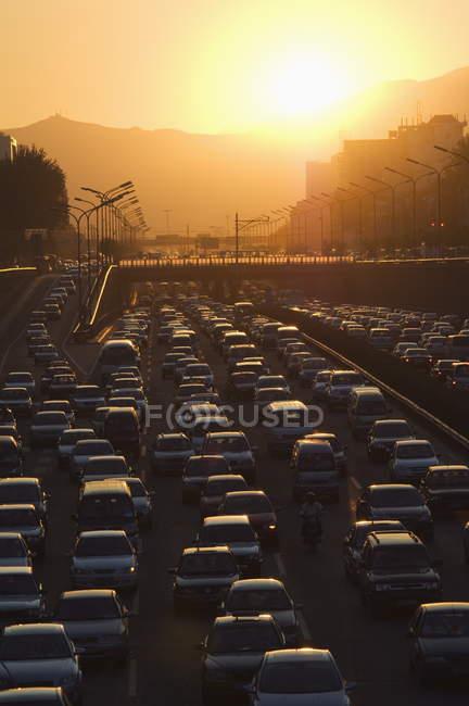 Захід сонця над кільцевій дорозі міста в годину пік — стокове фото