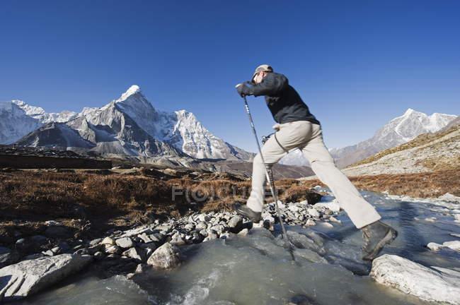 Ruscello di montagna di attraversamento Trekker — Foto stock