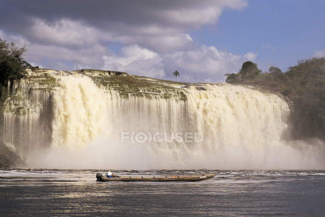 Waterfall and fishing boat on foreground — Stock Photo
