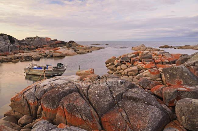 Червоний лишайниками на скелях і швартується човен — стокове фото