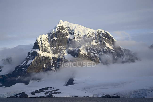 Snow covered coastal mountain — Stock Photo