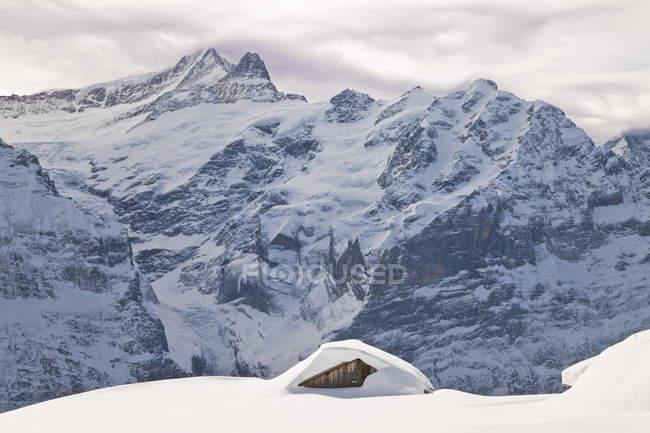 Cobertas de neve cabana na encosta da montanha — Fotografia de Stock