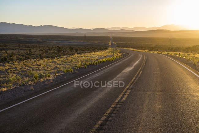 Longue route au coucher du soleil à l'est du Nevada — Photo de stock