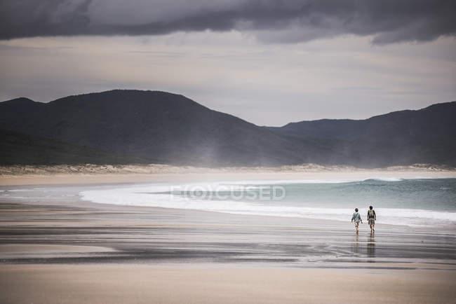 Пара ходьба на узбережжі в духів Bay — стокове фото