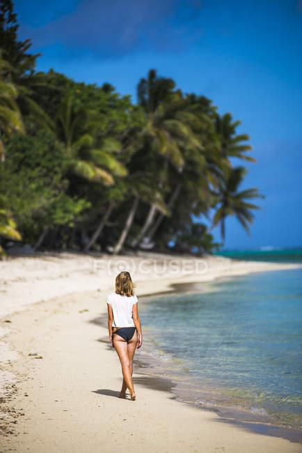 Donna che cammina lungo la spiaggia — Foto stock
